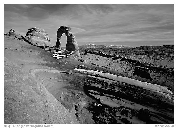 Sandstone bowl, Delicate Arch, and La Sal Mountains with snow, sunset. Arches National Park (black and white)