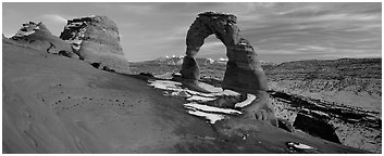 Desert Arch and mountains at sunset. Arches National Park (Panoramic black and white)