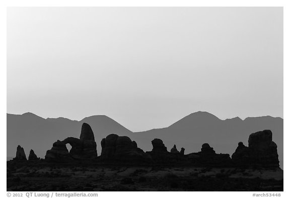 Turret Arch, spires, and mountains at dawn. Arches National Park (black and white)