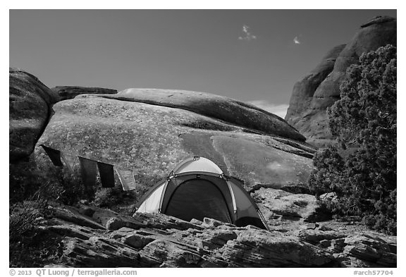 Tent with prayer flags amongst sandstone rocks. Arches National Park (black and white)