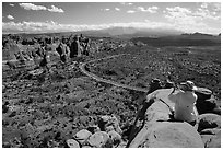 Tourist taking picture from top of fin. Arches National Park, Utah, USA. (black and white)