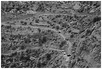 Jeep caravan negotiates hairpin turn on the Flint Trail,  Orange Cliffs Unit, Glen Canyon National Recreation Area, Utah. USA ( black and white)