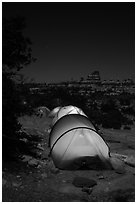 Lit tents at night in the Dollhouse. Canyonlands National Park, Utah, USA. (black and white)