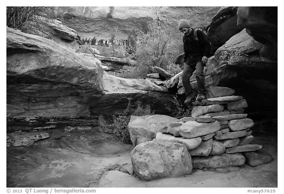 Hiker stepping down on primitive stairs, Maze District. Canyonlands National Park (black and white)