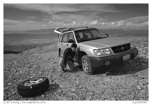 Man changing a flat tire on remote spot at top of Mt Washington. Great Basin National Park (black and white)