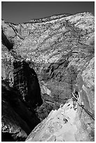 Woman hiker clinging to cable on Hidden Canyon trail. Zion National Park ( black and white)