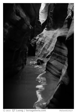Canyoneer in dark flooded Pine Creek Canyon. Zion National Park (black and white)