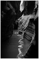 Canyoneer in dark flooded Pine Creek Canyon. Zion National Park ( black and white)