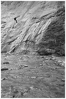 Canyoneer rappelling alongside Mystery Falls, the Narrows. Zion National Park, Utah, USA. (black and white)