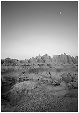 Mud cracks, badlands, and moon at dawn. Badlands National Park, South Dakota, USA. (black and white)