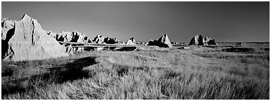 Badlands raising in tall grass prairie landscape. Badlands National Park (Panoramic black and white)