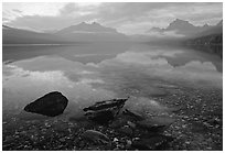 Rocks, peebles, and mountain reflections in lake McDonald. Glacier National Park, Montana, USA. (black and white)