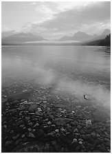 Pebbles, lake Mc Donald, and foggy mountain range, early morning. Glacier National Park, Montana, USA. (black and white)