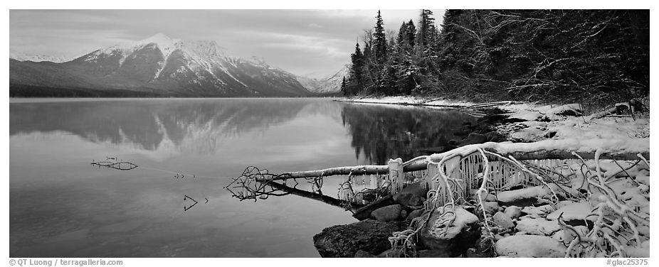 Lake, snowy shore, and mountains in winter. Glacier National Park (black and white)