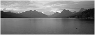 Mountains rising above calm lake in the evening. Glacier National Park (Panoramic black and white)