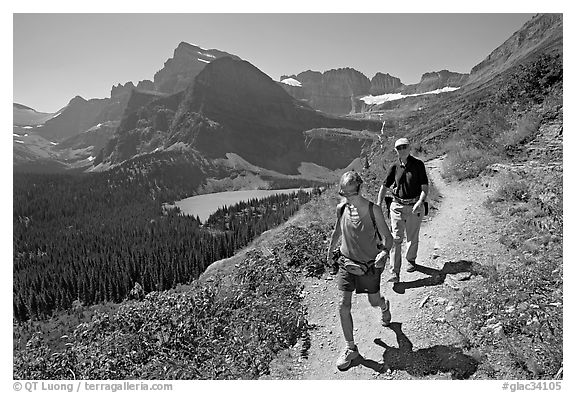 Couple hiking on trail, with Grinnell Lake below. Glacier National Park (black and white)