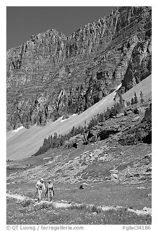 Couple hiking on trail amongst wildflowers near Hidden Lake. Glacier National Park (black and white)