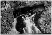 Water flows of opening in cliff face, Running Eagle Falls. Glacier National Park ( black and white)