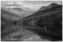 Kayaker paddling back to shore as clouds threaten, Kintla Lake. Glacier National Park ( black and white)