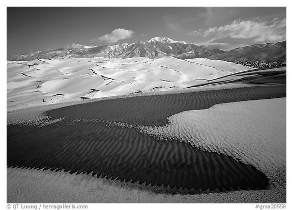 Patch of sand, snow-covered dunes, Sangre de Christo mountains. Great Sand Dunes National Park (black and white)
