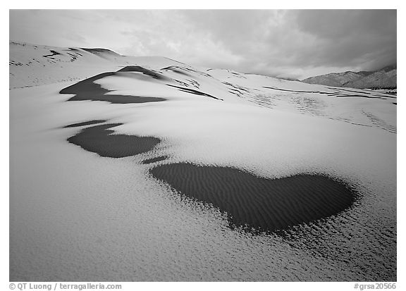 Patch of sand in snow-covered dunes. Great Sand Dunes National Park (black and white)
