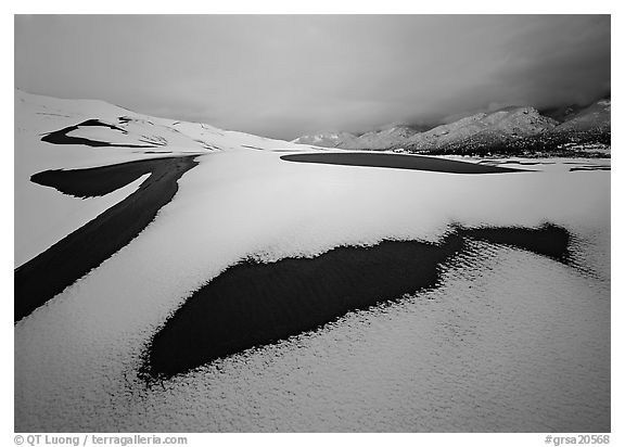 Patch of sand in snow-covered dunes. Great Sand Dunes National Park and Preserve (black and white)