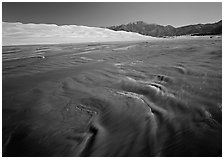 Medano creek with shifting sands, dunes and Sangre de Christo mountains. Great Sand Dunes National Park, Colorado, USA. (black and white)