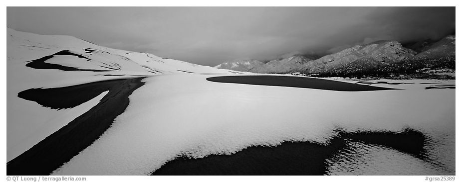 Snow-covered dune landscape and mountains at dawn. Great Sand Dunes National Park and Preserve (black and white)