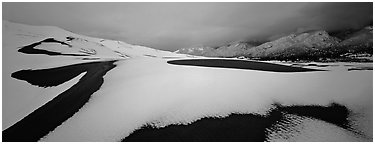 Snow-covered dune landscape and mountains at dawn. Great Sand Dunes National Park (Panoramic black and white)