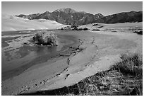 Banks of flowing Medano Creek, dunes and mountains. Great Sand Dunes National Park and Preserve ( black and white)
