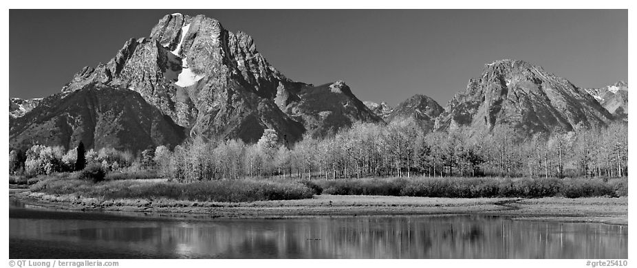 Rugged mountains rising above tree-lined lake in autumn. Grand Teton National Park (black and white)