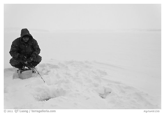 Man ice fishing on frozen Jackson Lake. Grand Teton National Park (black and white)