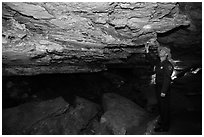 Ranger pointing at speleotherm in large cave room. Wind Cave National Park ( black and white)