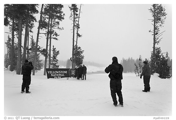 Tourists take pictures with entrance sign in winter. Yellowstone National Park (black and white)