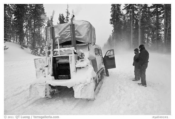 Couple standing in snowdrift next to snow coach. Yellowstone National Park (black and white)