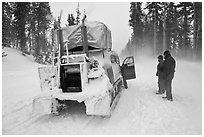 Couple standing in snowdrift next to snow coach. Yellowstone National Park, Wyoming, USA. (black and white)