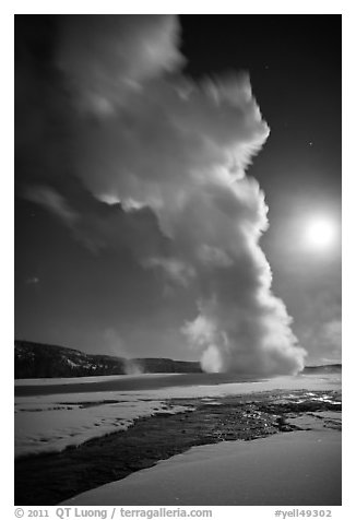 Old Faithful Geyser in the winter with moon. Yellowstone National Park (black and white)