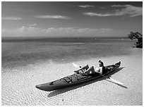Woman reclining in kayak on shallow waters,  Elliott Key. Biscayne National Park, Florida, USA. (black and white)