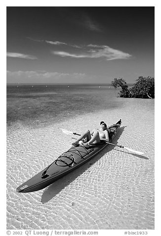 Woman sunning herself on sea kayak parked on shore,  Elliott Key. Biscayne National Park (black and white)