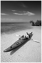 Woman sunning herself on sea kayak parked on shore,  Elliott Key. Biscayne National Park, Florida, USA. (black and white)