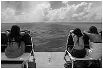 Women sunning themselves on snorkeling boat. Biscayne National Park, Florida, USA. (black and white)