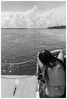 Woman relaxes on snorkeling boat as it enters Caesar Creek. Biscayne National Park, Florida, USA. (black and white)
