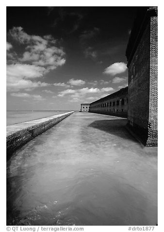 Fort Jefferson moat and massive brick wall on a sunny dayl. Dry Tortugas National Park (black and white)