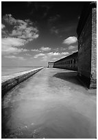Fort Jefferson moat and massive brick wall on a sunny dayl. Dry Tortugas National Park, Florida, USA. (black and white)