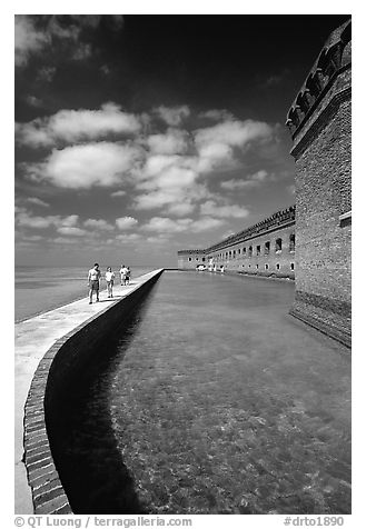 Tourists walking on seawall. Dry Tortugas National Park (black and white)