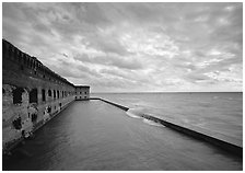 Fort Jefferson brick rampart and moat with wave over seawall, cloudy weather. Dry Tortugas National Park, Florida, USA. (black and white)
