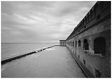 Fort Jefferson massive brick wall overlooking the ocean, cloudy weather. Dry Tortugas National Park, Florida, USA. (black and white)