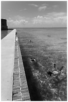 Snorkelers next to Fort Jefferson seawall. Dry Tortugas National Park, Florida, USA. (black and white)