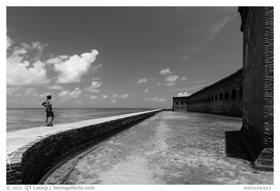 Park visitor looking, Fort Jefferson moat and seawall. Dry Tortugas National Park (black and white)