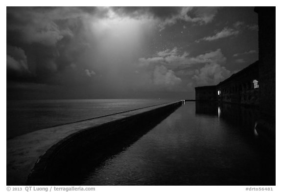 Fort Jefferson seawall at night with sky lit by thunderstorm. Dry Tortugas National Park (black and white)